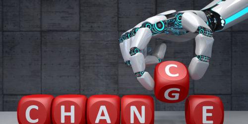 Roboterarm legt mit beschrifteten Würfeln den Schriftzug Change