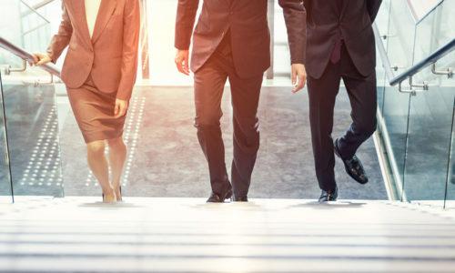 Drei Business Menschen laufen eine Treppe hinauf