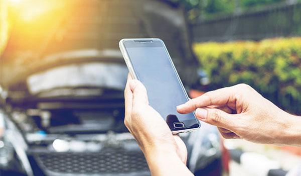 Person mit Handy in der Hand steht vor Auto mit geöffneter Motorhaube