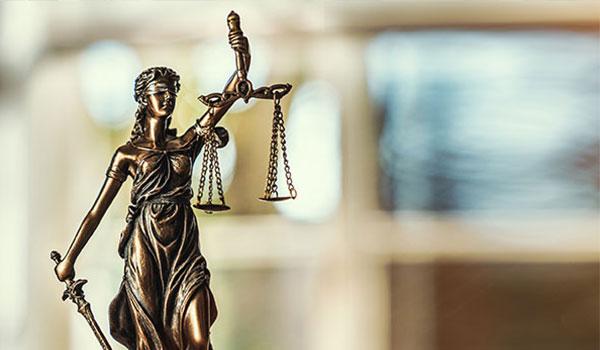 Justitia Figur steht auf einem Tisch