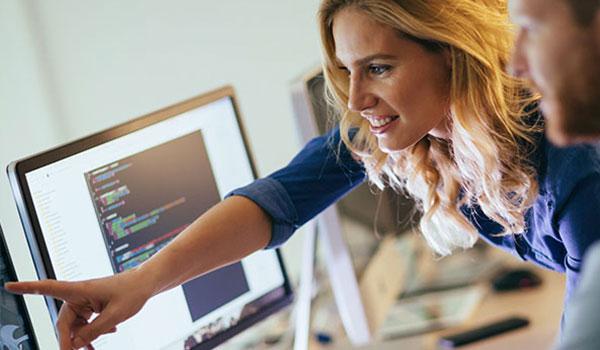 Frau und Mann besprechen sich am Computer im Büro