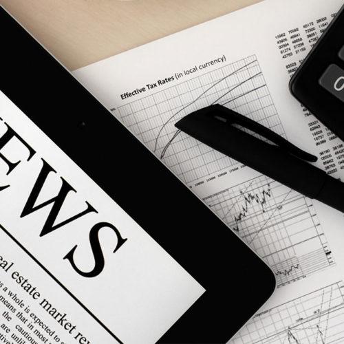 Tablet, Stift und Taschenrechner liegen auf einem Blatt mit Aktienkursen