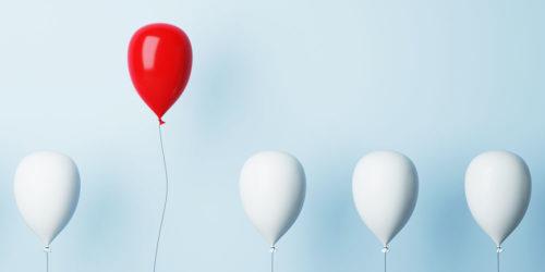 Aufsteigende weiße Luftballons, einer davon ist rot