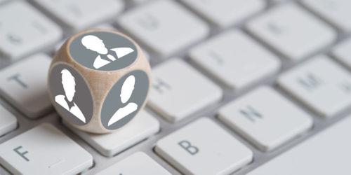 Würfel mit Personensymbolen liegt auf Tastatur
