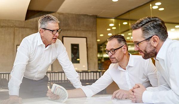 DATAGROUP Managers Max H.-H. Schaber, Dirk Peters und Andreas Baresel am Schreibtisch