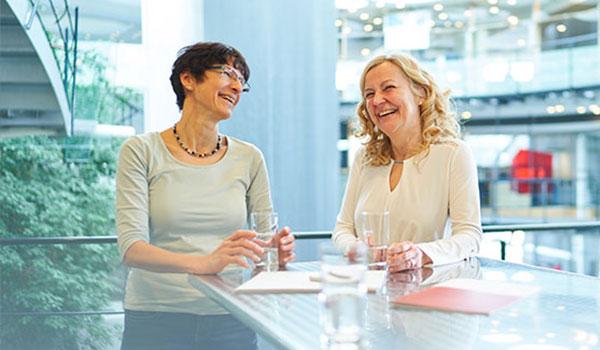 Zwei DATAGROUP Mitarbeiterinnen stehen am Stehtisch und lachen