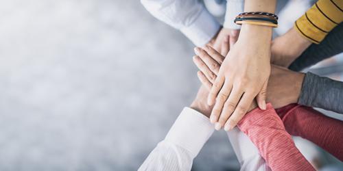 Gemeinsam anpacken: Hände zusammenlegen