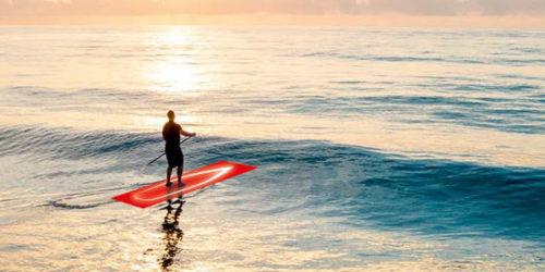 Stand-Up Paddler auf rotem Board paddelt ins Meer
