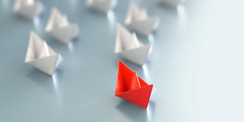 Rotes Papierschiffchen fährt vor weißen Papierschiffchen