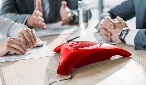 Drei Männer sitzen an einem Konferenztisch, es sind nur ihre Hände zu sehen. In der Mitte des Tisches ist ein rot gefärbtes Konferenztelefon.