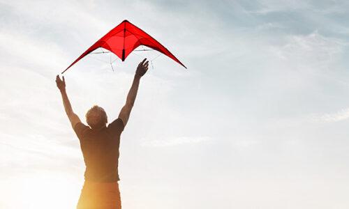 Ein Mann lässt einen roten Drachen in den Himmel steigen.