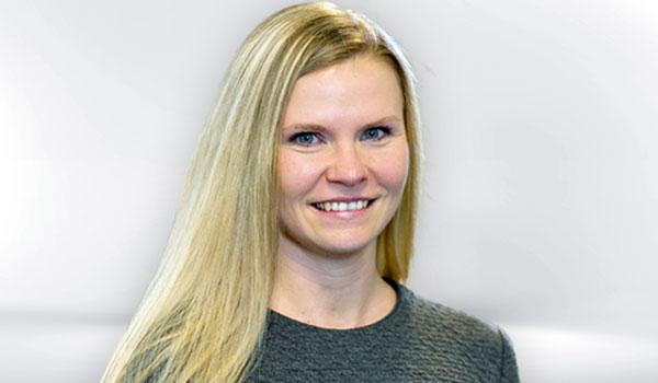 Portrait von Susanne Henkert, einer Frau mit langen blonden Haaren vor hellem Hintergrund